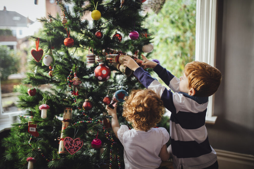 Two young children decorating a Christmas tree